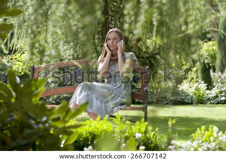 Tensed young woman using cell phone on bench in park - stock photo