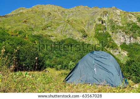 Tent against the backdrop of the magnificent mountain range - stock photo