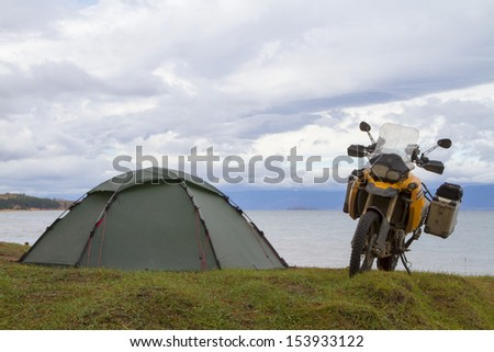 Tent and motorcycle traveler on the shores of Lake Baikal - stock photo