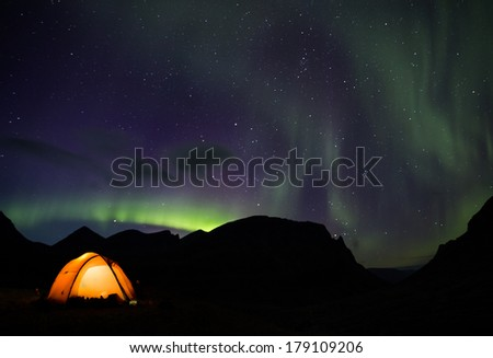 Tent and northern lights with the Nallo Mountain in the background in Sweden - stock photo