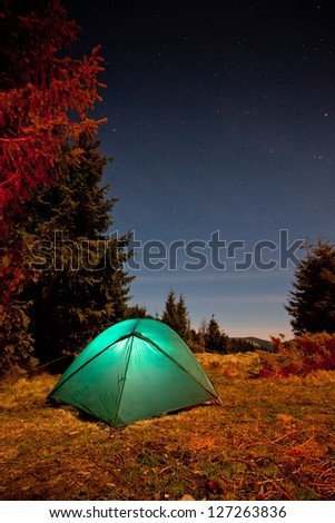 Tent illuminated with light in night forest - stock photo