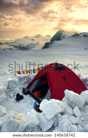 tent in high mountains with sundown and snow - stock photo