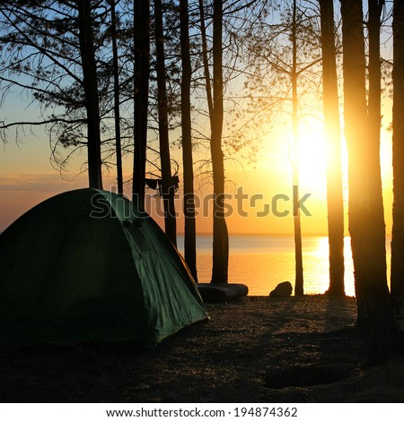 Tent in the Forest at the Seaside on Sunset Background - stock photo