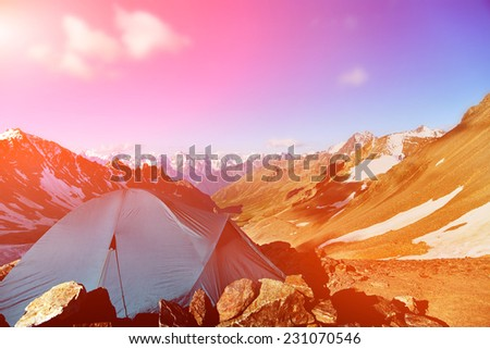 tent in the mountains. alpine camp. summer hiking - stock photo