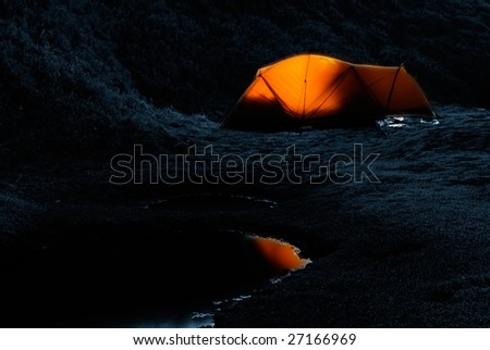Tent in the night with weak light and small lake. - stock photo