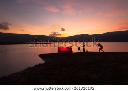 tent in the sunset near the lake with two silhouette of people. - stock photo