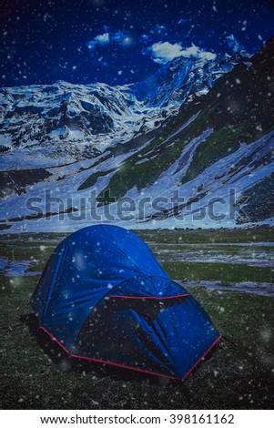 Tent pitched on a meadow at Nanga Parbat base camp at night during snowfall - stock photo
