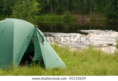 Tent set up for camping in wood by a river - stock photo