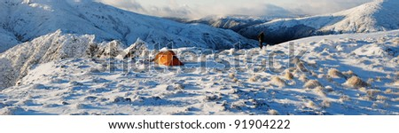 tent set up in snow with mountains - stock photo