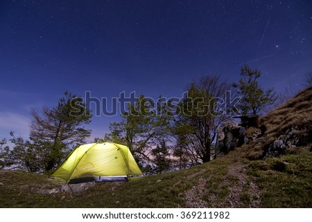 Tent standing on a mountain under the starry sky - stock photo