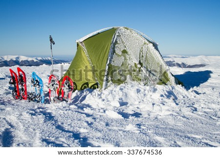 Tent winter mountains.Tent stands in the mountains in the snow. Snowshoes are beside the tent. - stock photo