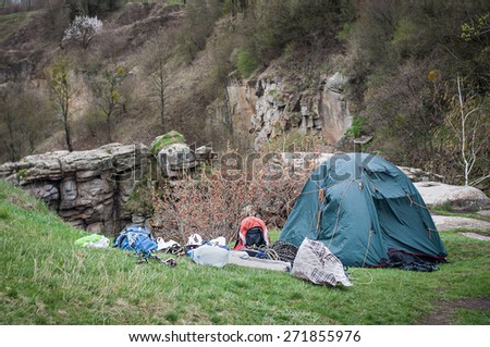 tent with touristic equipment at the top of the hill with cliff view - stock photo