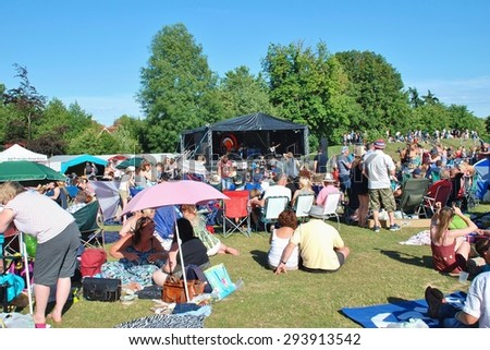 TENTERDEN, ENGLAND - JULY 4, 2015: The audience sit on the grass during the annual free Tentertainment music festival. The community event was first held in 2008. - stock photo