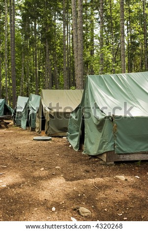 Tents at summer camp. A group of five tents in a clearing at a Boy Scout summer campsite. - stock photo