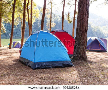 Tents of traveler in camping site near lake - stock photo