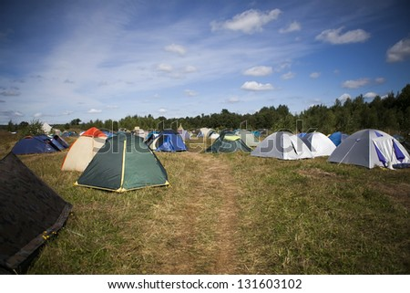 tents on a grass under white clouds - stock photo
