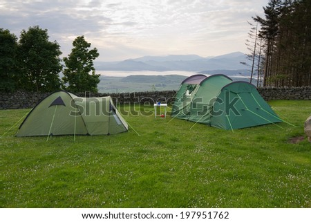 Tents on Welsh hillside with a view over coastal estuary of the River Dwyryd to Portmerion and the Snowdon mountain range in Wales, UK.  - stock photo