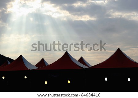 Tents under oblique beams of the sunset. - stock photo