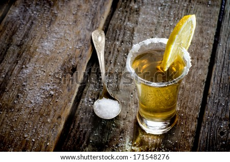 tequila and lemon on a wood background - stock photo