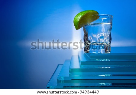 tequila and lime on a glass table. - stock photo