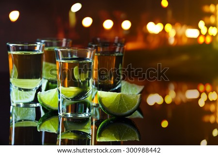 tequila and lime on glass table in bar - stock photo