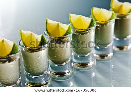tequila and lime on wet glass table - stock photo