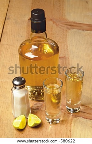 tequila bottle and shots on a wood table - stock photo