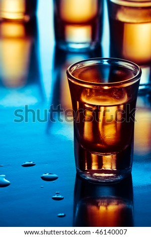 tequila drink on tap room in blue light - stock photo
