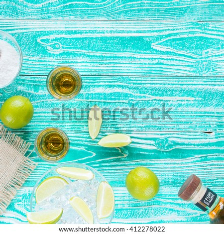 tequila in glasses and lime fruits on turquoise colored wooden table, top view - stock photo