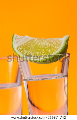 Tequila shot with a slice of lime on the glass on  orange background. Selective Focus - stock photo