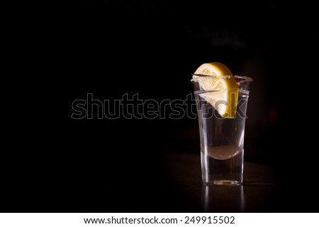 Tequila shot with lemon on the dark background. Shallow DOF - stock photo