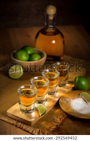 Tequila shots grouped together with a bottle and cut limes on a restaurant bar table