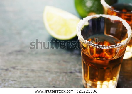 Tequila shots with lime and salt on rustic  background  - stock photo