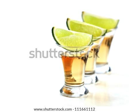Tequila shots with lime on white background.