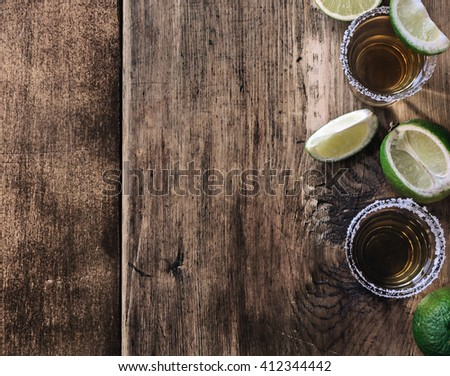 Tequila shots with lime slice on dark wooden rustic table. top view - stock photo