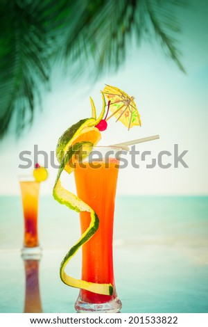 Tequila sunrise and long island cocktails with fruits and umbrella decoration at tropical ocean beach with palm trees. Vintage style, hipster colors image with copy space for party invitation text - stock photo