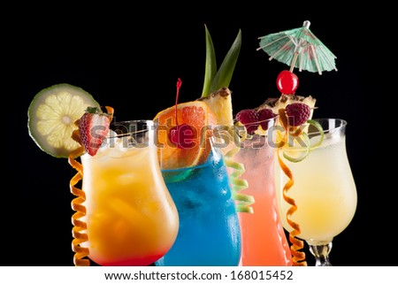 Tequila Sunrise, Blue Lagoon, Rum Runner, and Bahama Mama cocktails over black background on reflection surface, garnished with strawberry, lime, pineapple flag, fresh raspberry, maraschino cherry  - stock photo