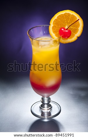 Tequila sunrise Cocktail in front of different colored backgrounds - stock photo