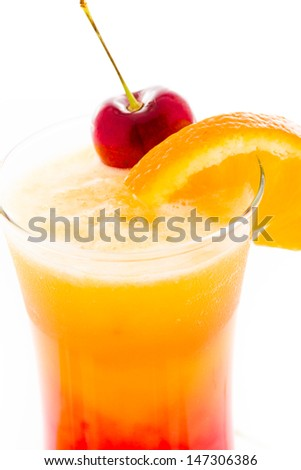 Tequila sunrise cocktail with orange wedge and cherry as a garnish. - stock photo