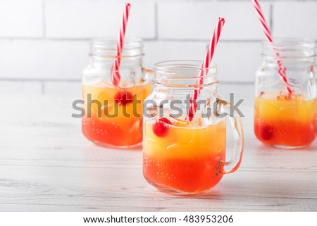 Tequila sunrise cocktails in glass jar with garnish