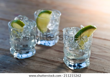 tequila with ice and lime on  old wooden table - stock photo