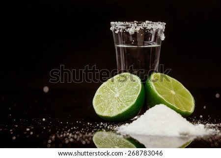 Tequila with lime and salt on black background - stock photo