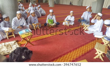 Terengganu , Malaysia - December 11, 2015 : Children at school classroom in Masjid do some memorize dexercises Quran in school holidays for better muslim life.  - stock photo