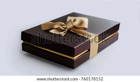 Terra cotta present box with gold ribbon on flower background