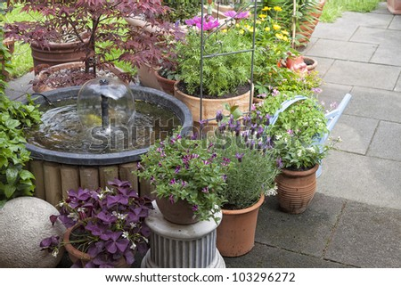 terrace at a allotment  garden with various flowerpots  and a water fountain. - stock photo