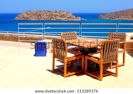 Terrace sea view with outdoor wood chairs and table in a luxury resort(Crete, Greece)Horizontal image - stock photo