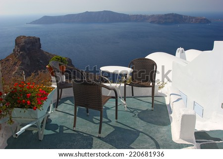 Terrace with chairs and a table. View to the caldera in Santorini island, Greece - stock photo