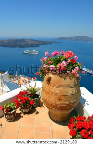 Terrace with flowers and view over the cruise ships on Santorini Bay, Greece - stock photo