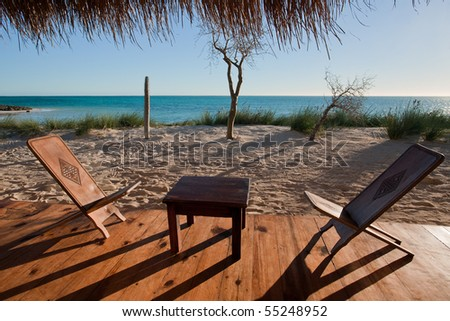 Terrace with wooden chairs, overlooking the lagoon