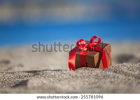 Terracotta color gift box on a beach - stock photo
